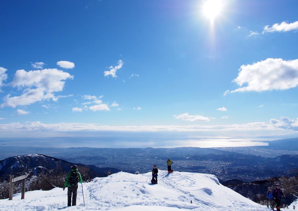 雪の塔ノ岳山頂から見る相模湾が太陽の光を照らす